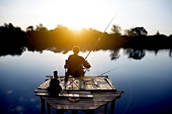 Rybář chytající při západu slunce